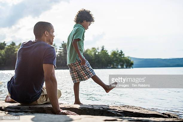 A father and son on a lake shore in summer.