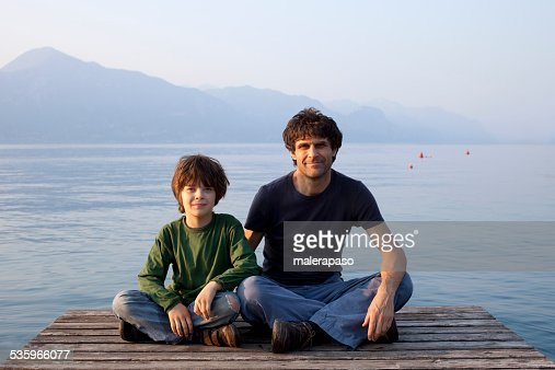 Father and son on a sitting on pier : Stock Photo