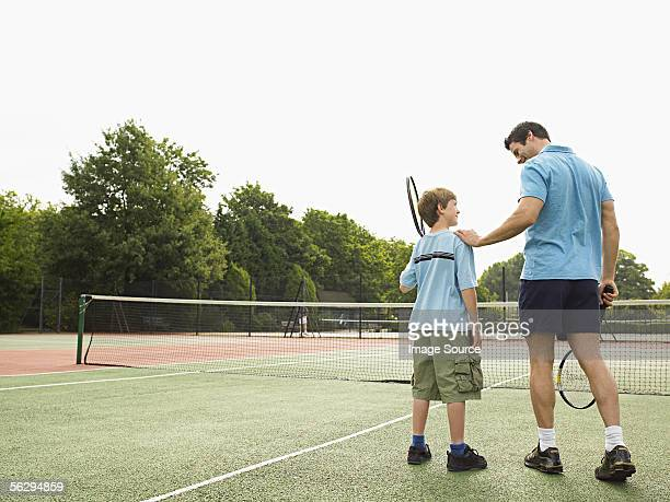 Father and son on a tennis court