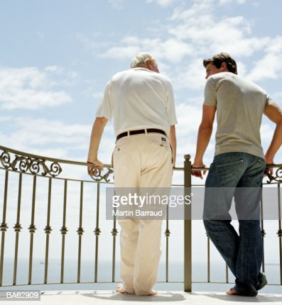Father and son on balcony, rear view : Bildbanksbilder