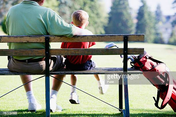 Father and Son on Bench at Golf Course
