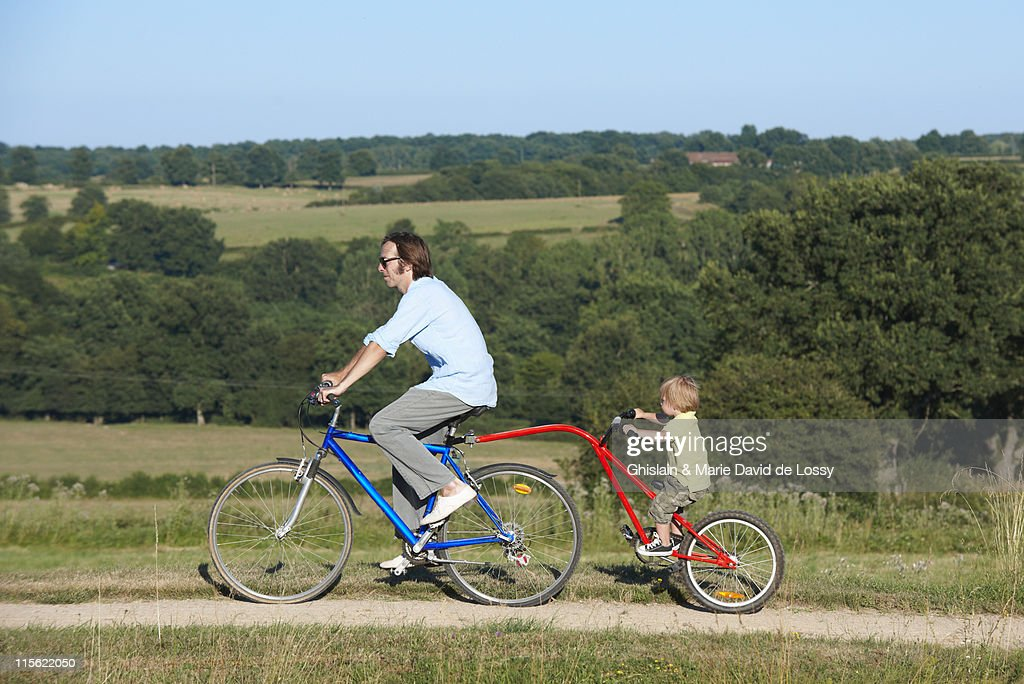 Father and son on bicycle in the fields : Stock Photo