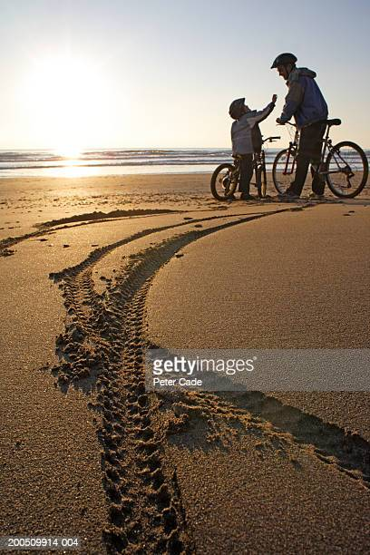 Father and son (6-8) on bicycles on beach, tracks in foreground