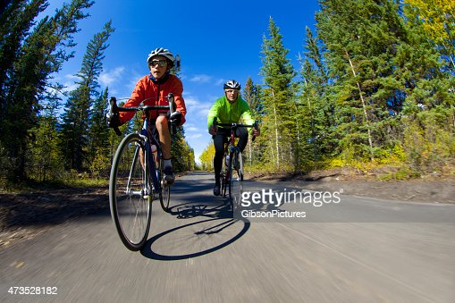 Father and son on bicycles road biking