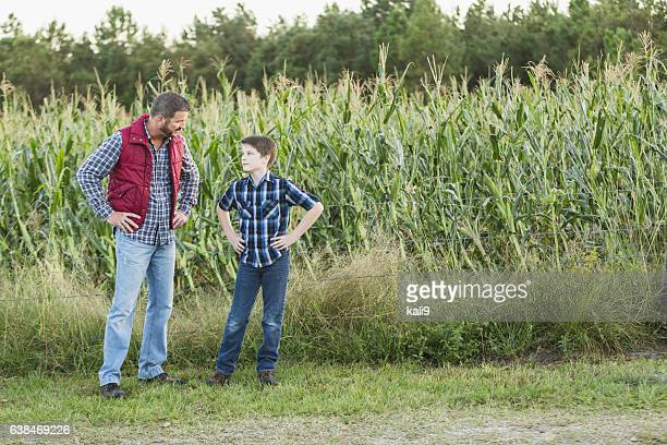 Father and son on family farm, in field of corn