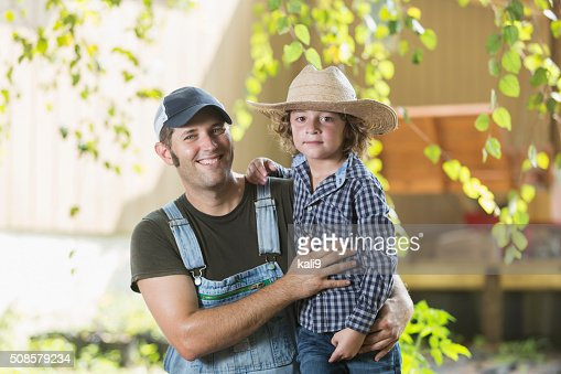 Father and son on family farm smiling at camera : Stock Photo