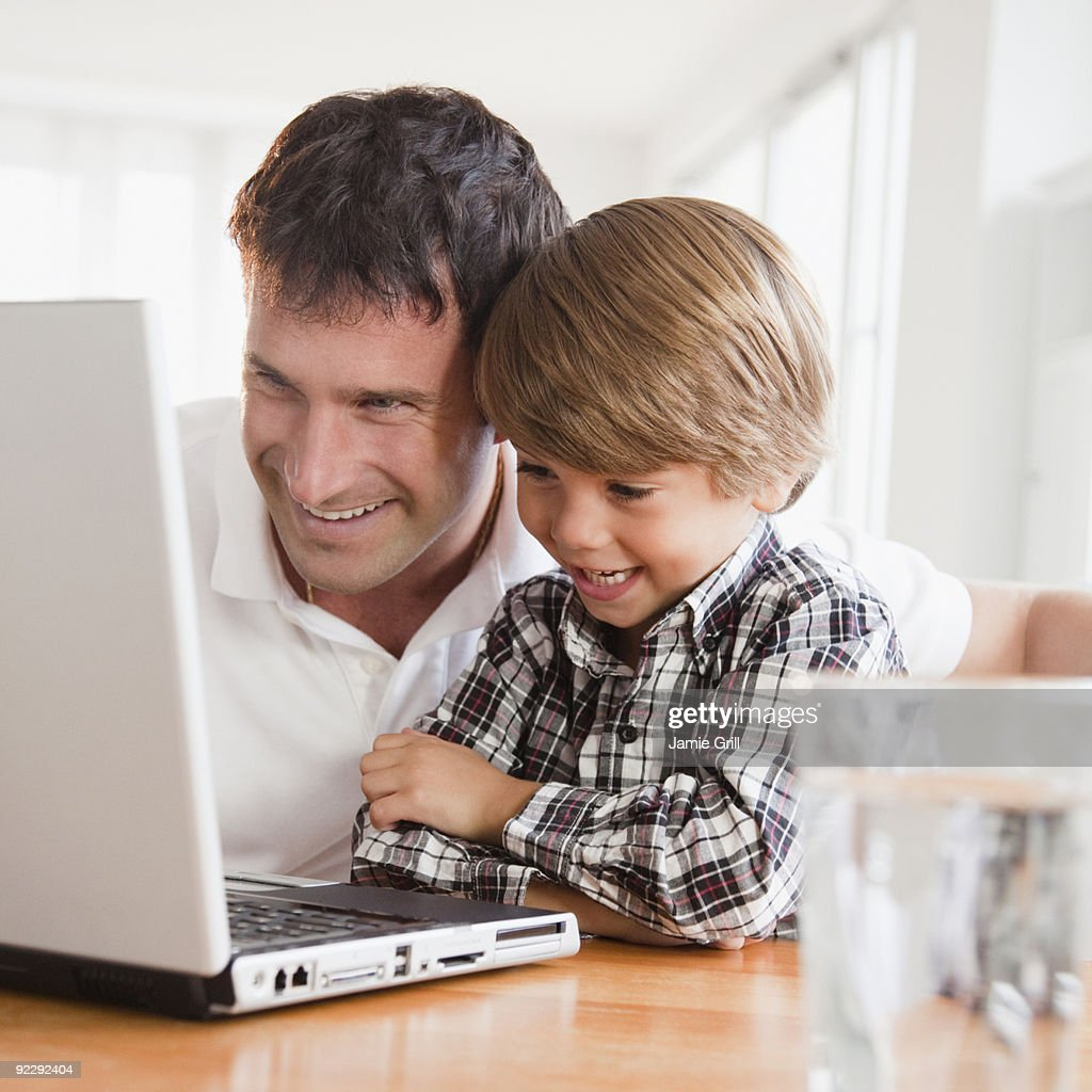 Father and son on laptop together : Stock Photo