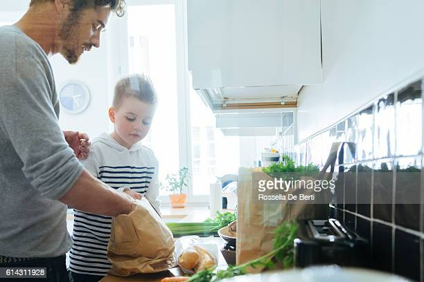 Father And Son Organizing Groceries In The Kitchen