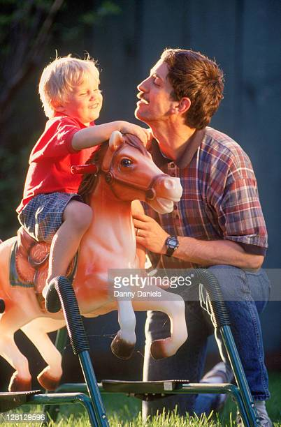 Father and son outdoors w/ rocking horse