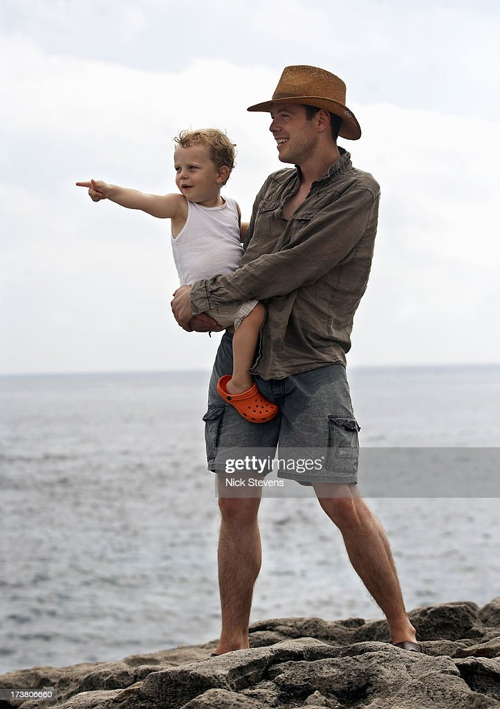 Father and son overlooking ocean : Stock Photo