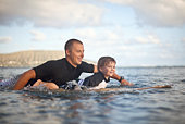 Father and son paddling on surfboard