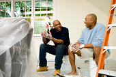 Father and son painting room, talking