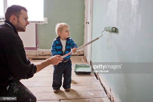 Father and son painting wall