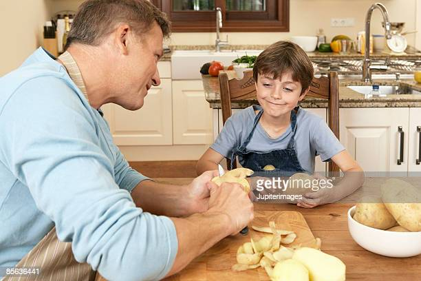 Father and son peeling potatoes in kitchen