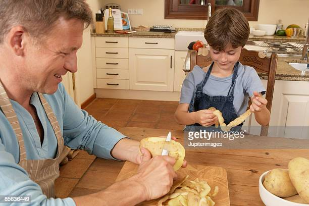 Father and son peeling potatoes