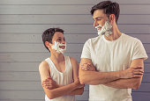 Handsome young father and his teenage son with shaving foam on their faces are looking each other and smiling, standing cross-armed against gray wall