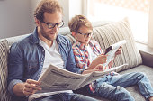 Father and son are reading newspapers and smiling while spending time together at home