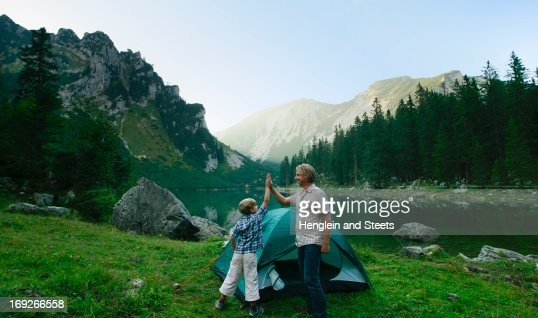 Father and son pitching tent together : Stock Photo
