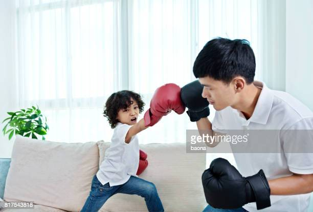 Father and son play boxing at home