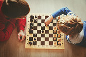 father and son play chess, kids learn and play activities