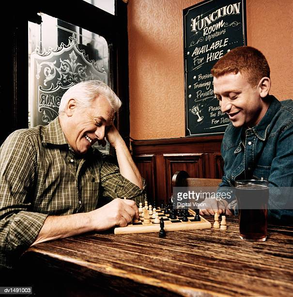 Father and Son Playing a Game of Chess Sitting at a Table in a Pub