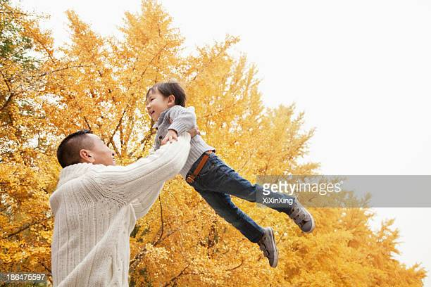 Father And Son Playing a Park in Autumn