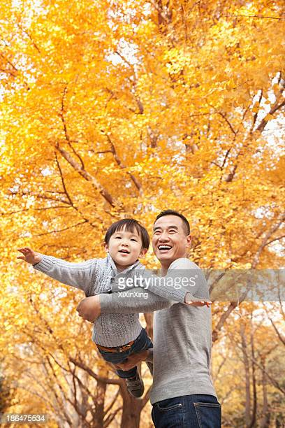 Father and Son Playing at Park in Autumn