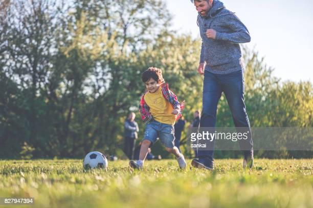 Vader en zoon op voetbal spelen bij het openbare park bij zonsondergang