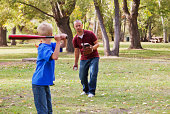 Father And Son Playing Baseball In A Park