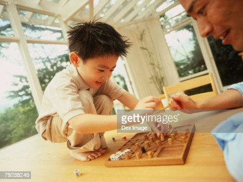 Father and son playing board game : Stock Photo