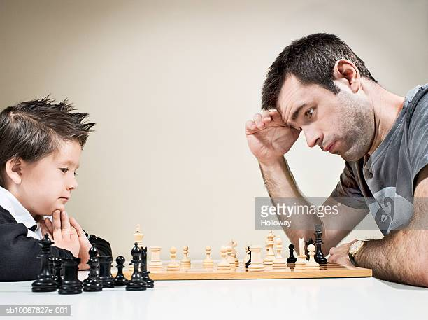 Father and son (4-5 years) playing chess, side view, close up