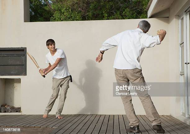 Father and son playing cricket on patio