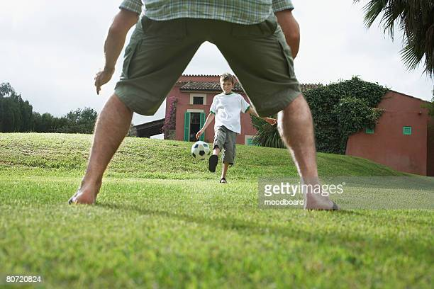 Father and son (5-6) playing football in back yard