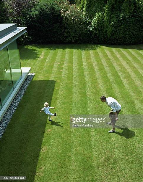 Father and son (2-4) playing football in garden, elevated view