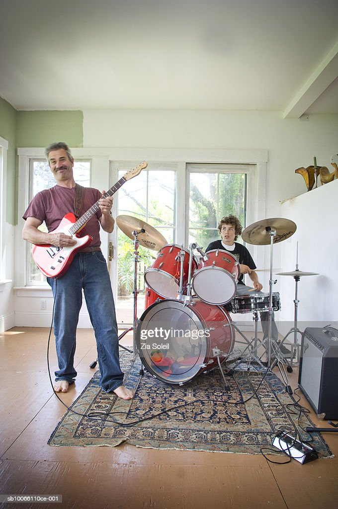 Father and son (14-15) playing guitar and drums, smiling : Stock Photo
