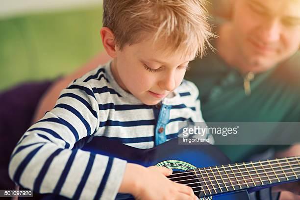 Vater und Sohn spielt Gitarre
