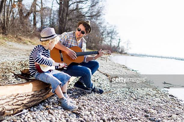 Father and son playing guitars by creek
