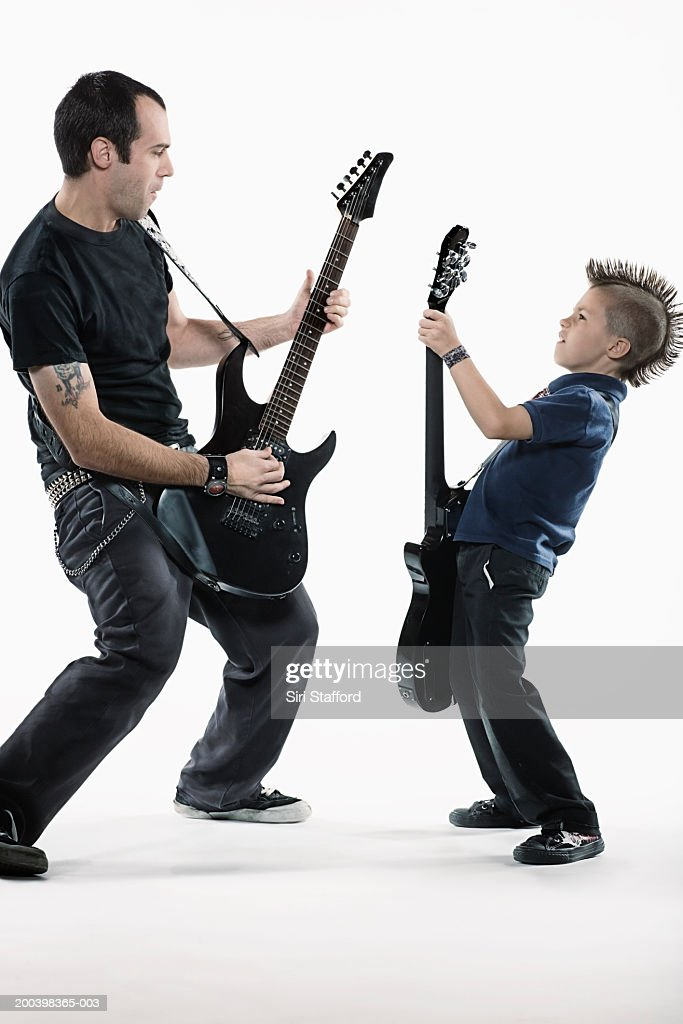 Father and son (8-10) playing guitars : Stock Photo