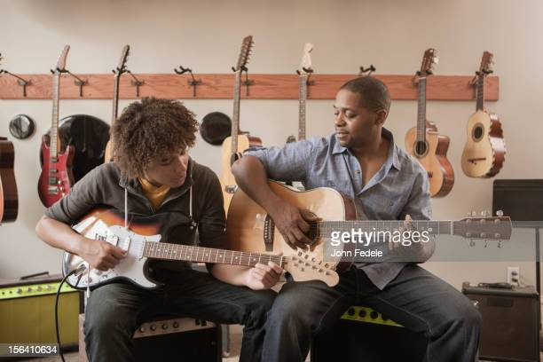 Father and son playing guitars together