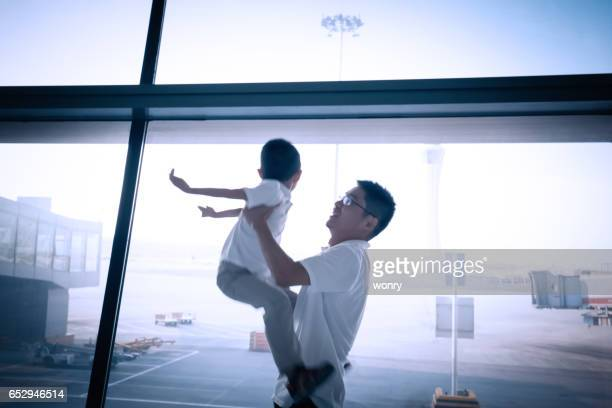 Father and son playing in airport lounge