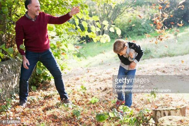 Father and son playing in Autumn leaves in park