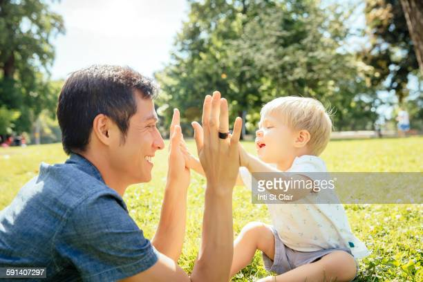 Father and son playing in grass in park