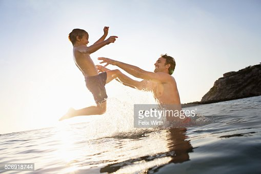 Father and son (6-7) playing in sea : Photo