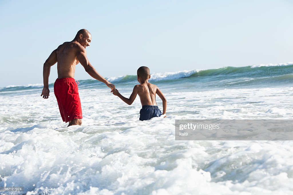 Father and son playing in surf : Stock Photo