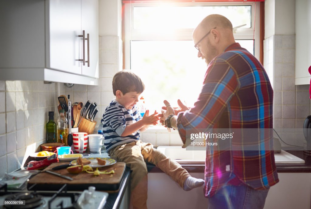 Father and son playing in the kitchen : Stock Photo