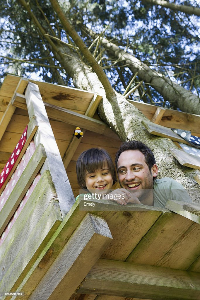 Father and son playing in tree house : Stock Photo