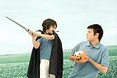 Father and son playing, man holding jack o' lantern, boy swinging sword