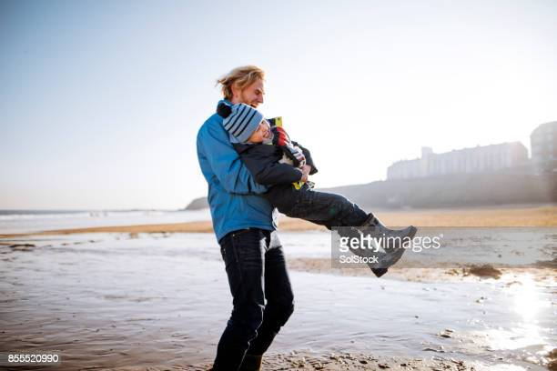 Father and Son Playing on a Cold Beach