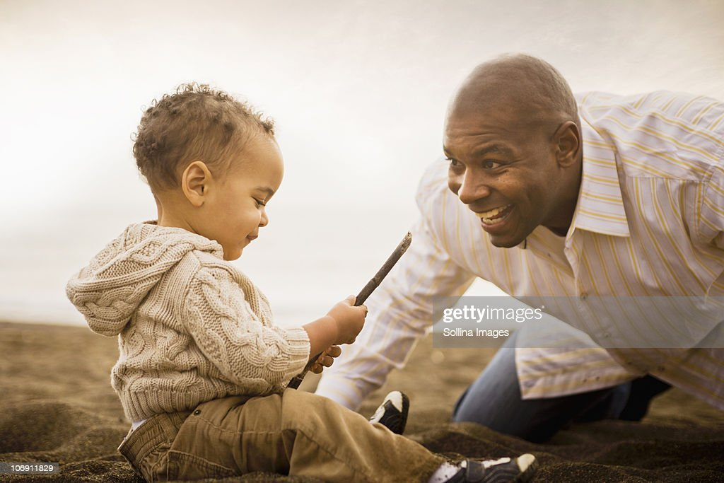 Father and son playing on beach : Stock Photo