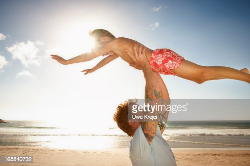 Father and son (6 - 8 years) playing on beach : Stock Photo